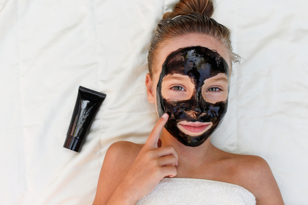 Beautiful girl with facial charcoal mask. Top view.