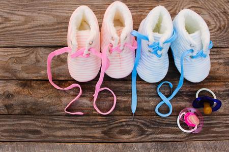 Nieuwjaar geschreven 2018 veters van kinderschoenen en fopspeen op oude houten. Afgezwakt beeld Stockfoto