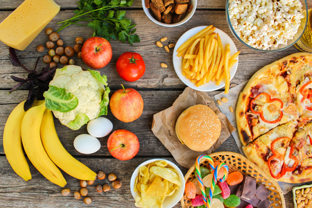 Fastfood and healthy food on old wooden background. Concept of eating. Top view. Stock Photo