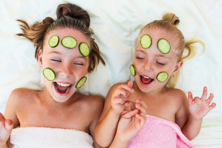 Beautiful girl with facial mask of cucumber. Toned image. Top view.