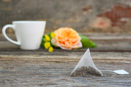 Tea bag on background of rose and cup of tea.