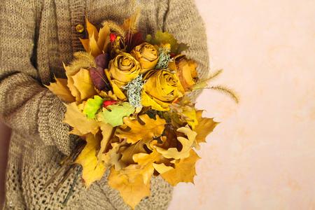 Girl holding autumn bouquet of yellow dry leaves. 版權商用圖片
