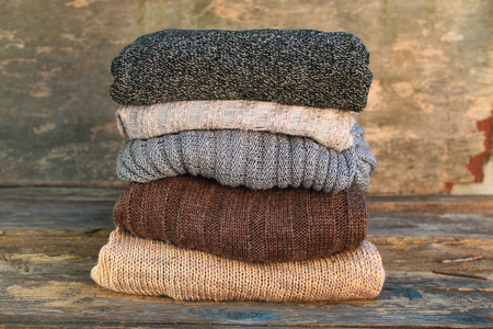 Pile of colorful warm clothes on wooden background. Standard-Bild