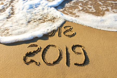 2019, 2018 years written on sandy beach sea. Wave washes away 2018.