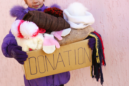 Girl holding donation box with warm winter clothes. Standard-Bild