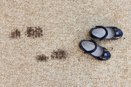 Dirty floor and children's shoes. Concept of child soiled carpet. 免版税图像 - 117263053