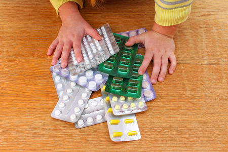 A small child playing with medicines.