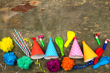 Holiday hats, whistles, balloons on old wooden background. Concept of childrens birthday party. Top view.