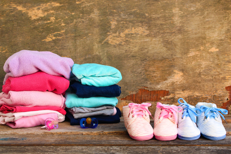 Baby shoes, clothing and pacifiers pink and blue on the old wooden background. Banco de Imagens