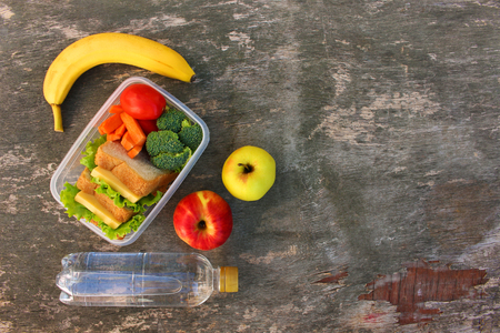 Sandwiches, fruits and vegetables in food box, water on old wooden background. Top view. Flat lay.