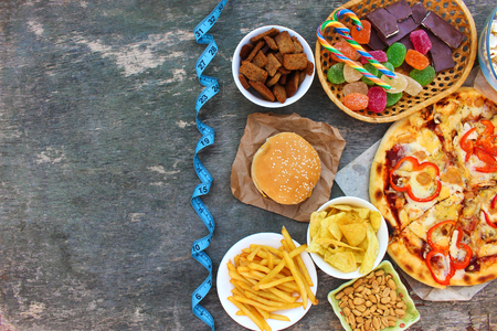 Fast food, tape measure on old wooden background. Concept of junk eating. Top view. Flat lay. Banco de Imagens