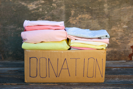 Donation box with clothes on the old wooden background. Banco de Imagens