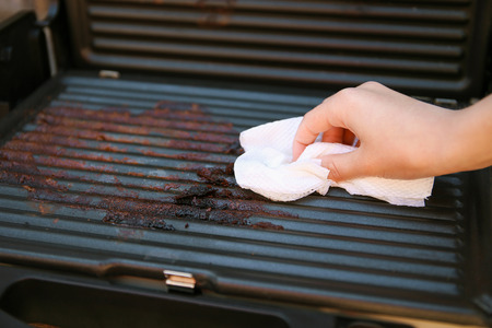 Dirty electric grill. Female hand wiping with cloth grill.