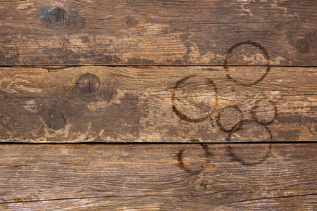 Trail from cups of coffee on old wooden background. Top view. Flat lay.