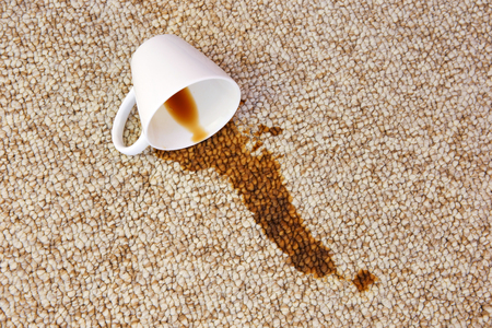 Cup of coffee fell on carpet. Stain is on floor. Фото со стока