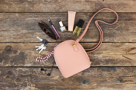 Things from open lady purse. Cosmetics and womens accessories fell out of handbag on old wooden background. Top view.