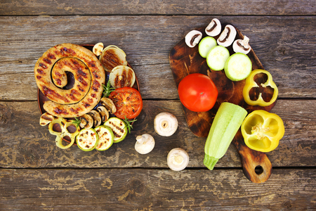 Grilled sausage and vegetables on old wooden background. Top view. Flat lay.