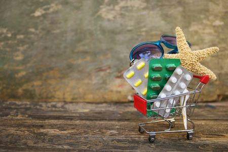 Shopping cart with pills, sunglasses, seashells on old wooden background. Concept of medication required in journey.