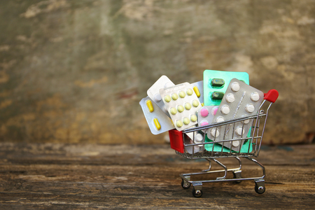 Shopping cart with pills on old wood background.