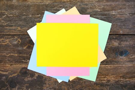 Colored sheets of paper on old wooden background. Top view. Flat lay.