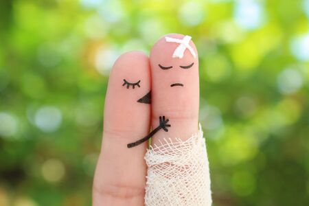 Fingers art of displeased couple. Man is sick, woman feels sorry for him. She kisses and hugs his. Banco de Imagens