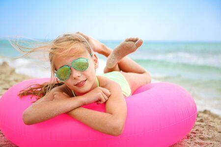 Happy girl lying on pink inflatable circle.