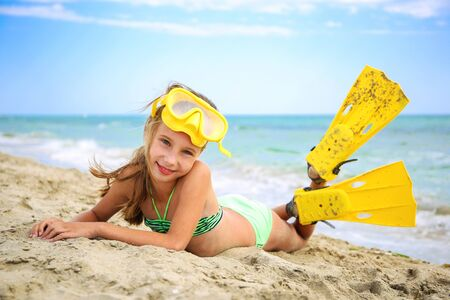 Girl sunbathing on beach in mask and fins for scuba diving. Banco de Imagens - 126667285