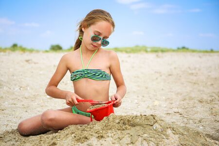 Child plays  with sand on beach.
