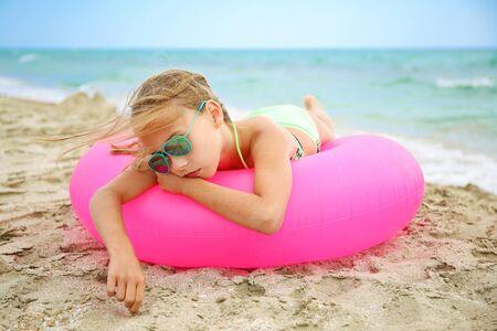 Sad girl lying on pink inflatable circle.