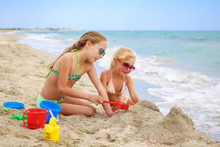 Children play with sand on beach.
