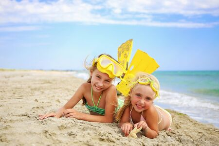 Girls sunbathing on beach in mask and fins for scuba diving.