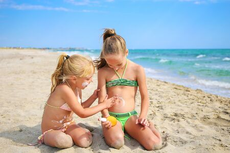 Sister applying protective sunscreen on young child. Girl draws sun cream on her stomach. Banco de Imagens - 131144849