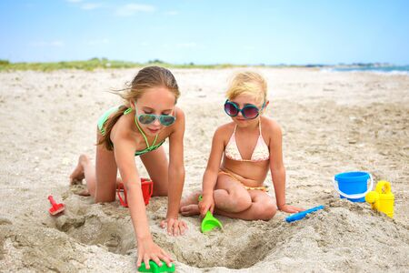 Children play with sand on beach. Banco de Imagens - 131144851
