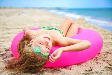 Happy girl sunbathing on beach. Banco de Imagens