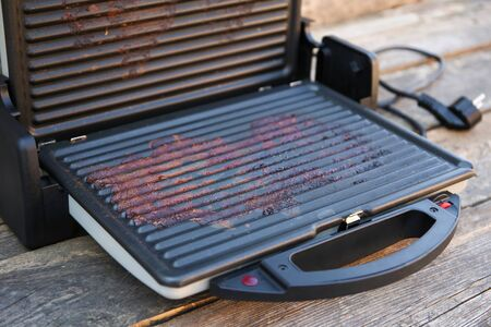 Dirty electric grill on old wooden background. Top view. Flat lay.