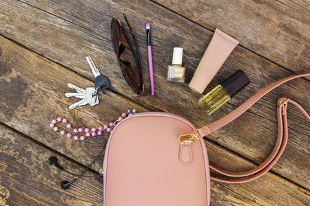 Things from open lady purse. Cosmetics and women's accessories fell out of handbag on old wooden background. Top view.