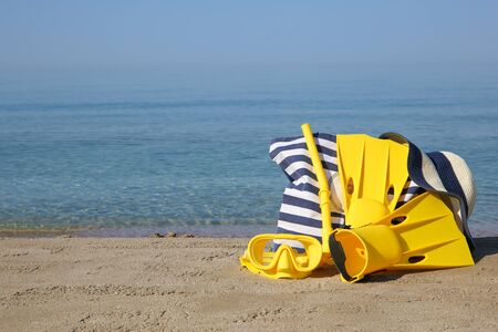 Mask and fins for scuba diving, summer womens accessories on beach.