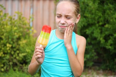 Girl has toothache from cold ice cream. Banco de Imagens - 131144927
