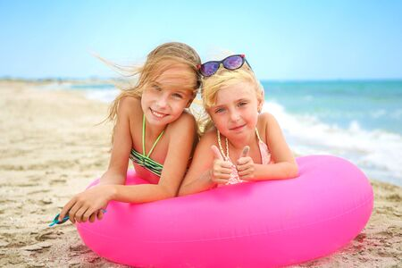 Happy girls lying on pink inflatable circle. Banco de Imagens