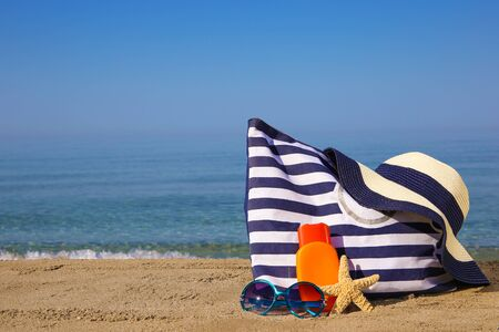 Summer women's accessories on the beach. Banco de Imagens - 131144929