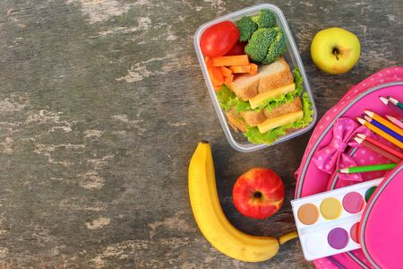 Sandwiches, fruits and vegetables in food box, backpack on old wooden background. Top view. Flat lay. Banco de Imagens
