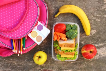 Sandwiches, fruits and vegetables in food box, backpack on old wooden background. Top view. Flat lay.