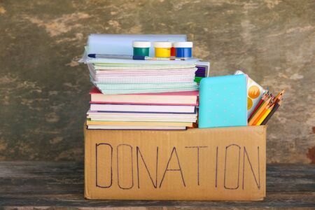 Donation box with school supplies on old wooden background. Banco de Imagens - 131144948