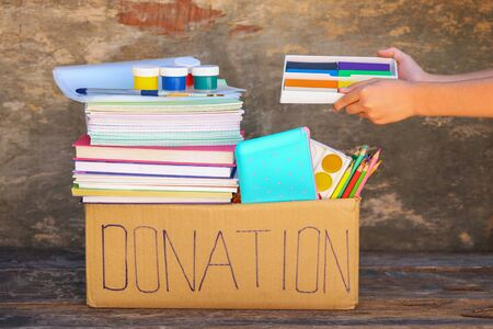 Donation box with school supplies on old wooden background. Banco de Imagens - 131144964