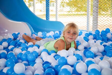 Girl playing with ball in playroom. Banco de Imagens