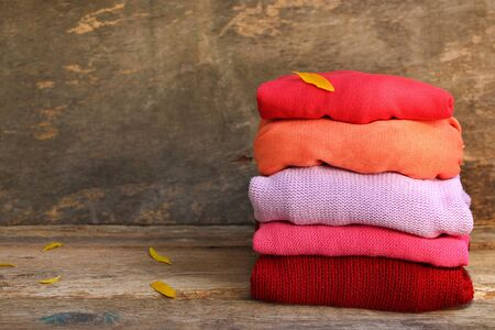 Pile of colorful warm clothes and yellow leaf on wooden background. Banco de Imagens - 131144972