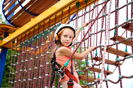 Happy girl on rope way in amusement center for children.