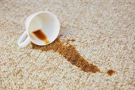 Kopje koffie viel op tapijt. Vlek zit op de vloer.