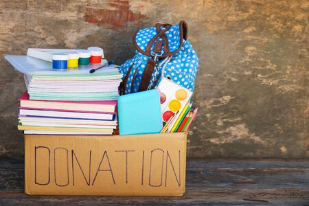 Donation box with school supplies on old wooden background.