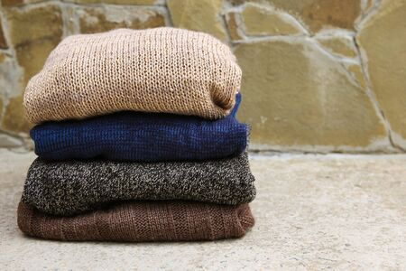 Pile of warm clothes on stone background. Banco de Imagens - 131144993